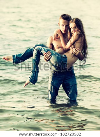Colorized vintage outdoor portrait of  beautiful romantic couple of topless girl and muscular guy in jeans posing in sea waters. guy holds girl on hands