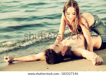 Colorized vintage outdoor portrait of  beautiful romantic couple of topless girl and muscular guy in jeans on beach - stock photo