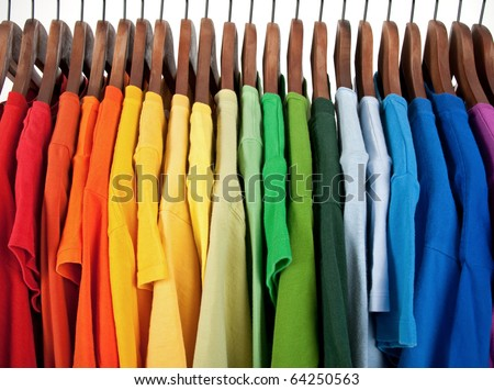 Colors of rainbow. Variety of casual clothes on wooden hangers, isolated on white. - stock photo