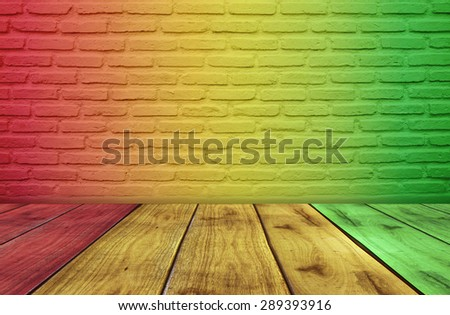 Colors of reggae music on brick wall background and wooden floor - stock photo