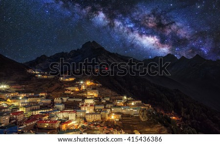 Colour night of the Sherpa village Namche Bazar with milky way over the mountain - Nepal Himalaya. Long exposure, excessive noise - stock photo
