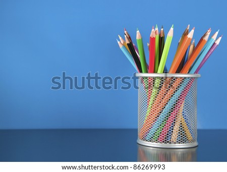 Colour pencils in the basket on the blue background