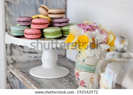 Coloured arrangement of macaroons and flowers on a wooden table - stock photo