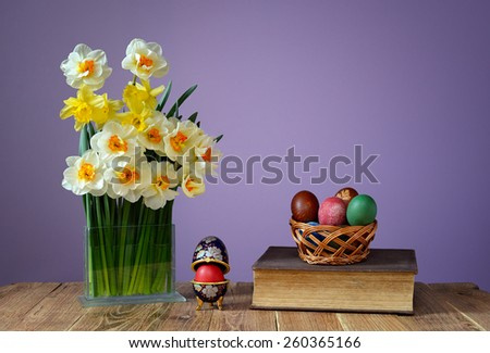 Coloured Easter eggs, books and flowers in a vase on the table - stock photo