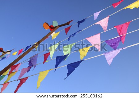 coloured flags on background of blue sky - stock photo