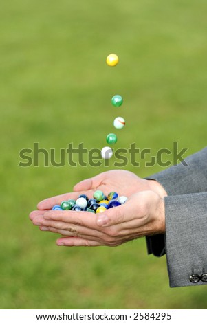 Coloured marbles dropping into a hand that is already full of marbles. Outdoors against a grassy background - stock photo