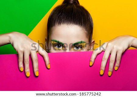Coloured paper and a beautiful girl's face - stock photo