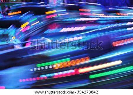 Colourful amusement funfair park ride with night lights blur - stock photo