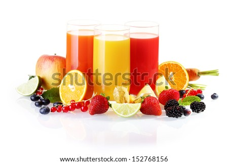 Colourful arrangement of fresh fruit including berries, citrus and apples with glasses of liquidised juice for a healthy start to the day - stock photo