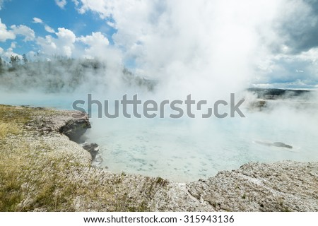 Colourful bacteria at the Grand Prismatic Spring in yellowstone national park, USA. Thermal pool of steaming water geyser on beautiful Summer's day - stock photo