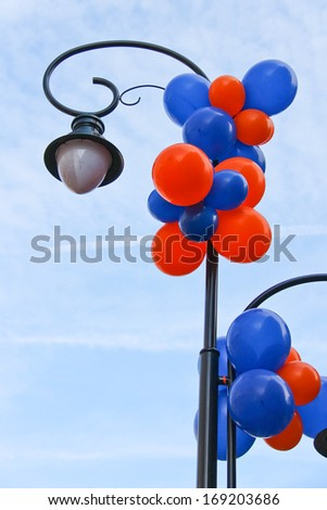 Colourful balloons adorn the column with lantern on a city street