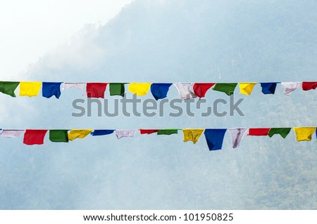 Colourful buddhist tibetan prayer flags waving in the wind at India.