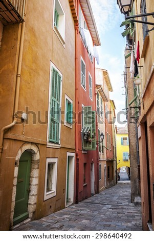Colourful buildings with bright window shutters along cobblestone street in old medieval town Villefranche-sur-Mer on French Riviera, France.