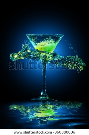 colourful cocktail in glass with splashes and lemon on dark background. Party club entertainment. Mixed light - stock photo