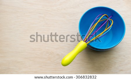 Colourful cute plastic whisk or egg beater and blue bowl on empty wooden surface. Concept of kitchen tool for kids or young chef. Slightly de-focused and close-up shot. Copy space. - stock photo