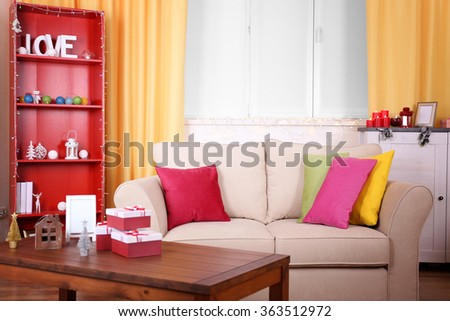 Colourful decorated interior. Comfortable living room, table with gift boxes on it is close up - stock photo