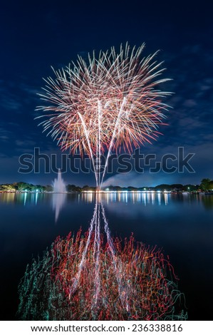 colourful fireworks on night sky with a reflection on the water for celebration - stock photo