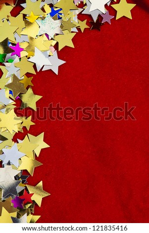 Colourful, glittering stars on red background. Christmas wishes or birthday message. Plenty of copy space, portrait orientation.