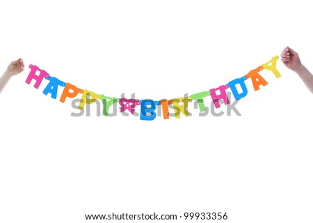 Colourful Happy Birthday banner being held midair by two hands in a celebration and party concept - stock photo