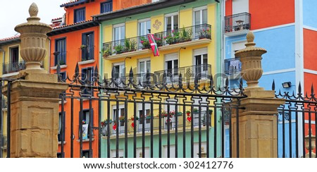 colourful houses behind fence with the basque flag hanging out in pamplona, basque country, spain, europe - stock photo