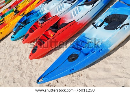 Colourful kayaks on the beach. - stock photo