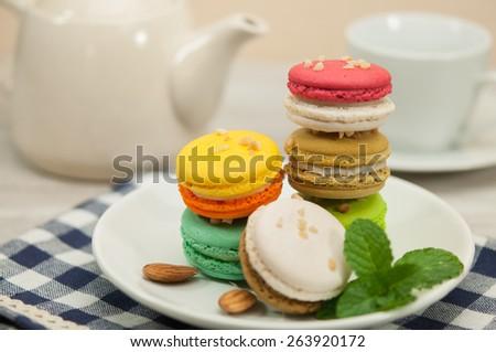 colourful macaron and teapot on table. - stock photo