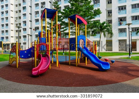 Colourful playground for children in public housing block in Singapore. Surrounded by green trees - stock photo
