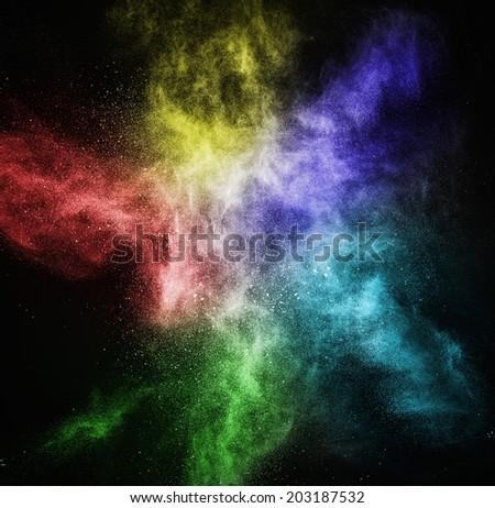 Colourful powder exploding isolated on black - stock photo