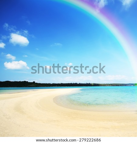 Colourful rainbow over a blue ocean with sandy beach in the foreground - stock photo