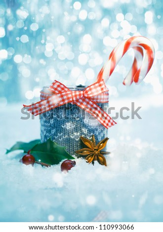 Colourful red and white striped Christmas candy canes with a matching checked ribbon and bow in snow with a bokeh of twinkling party lights - stock photo