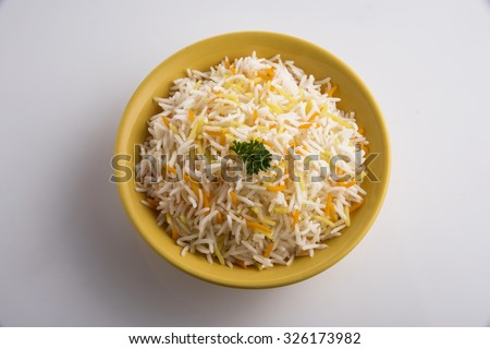 colourful rice, Indian rice dish or pulav, Shai Pilau or pulav or Indian colourful Biryani colorful pulav, in yellow bowl on white background, isolated, rice with coriander leaf  - stock photo