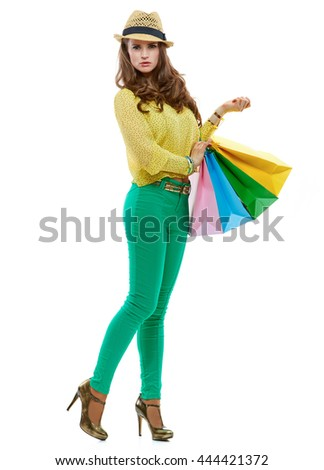 Colourful shopping vibes. Full length portrait of brunette woman in hat and bright clothes with colorful shopping bags posing against white background - stock photo