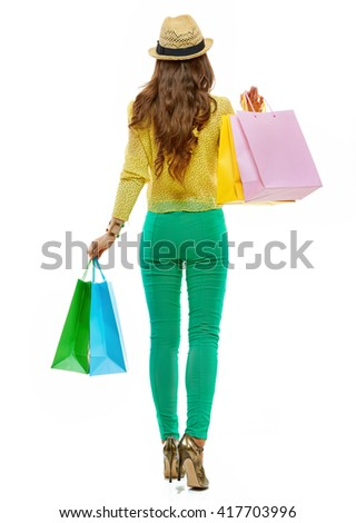 Colourful shopping vibes. Seen from behind in full length brunette woman in hat and bright clothes with shopping bags making step