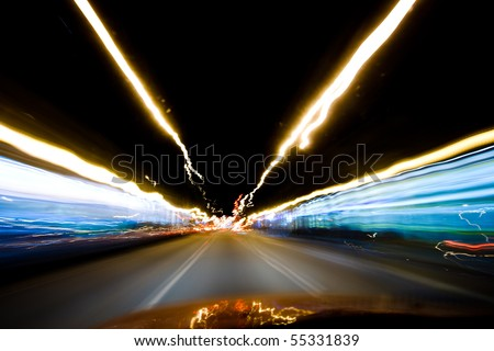 Colourful streaks of light converging on the horizon (long shutter speed while driving). - stock photo