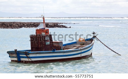 Colourful traditional fishing boats in harbour with the ocean and clouds in the background - stock photo