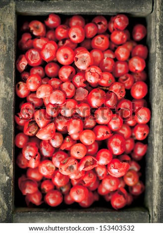 Colourful whole dried pink peppercorns with their red colouring used as a pungent spice and condiment in cooking, overhead view - stock photo