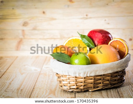 Colourful wicker basket of assorted tropical fruit with a lime, grapefruit, oranges and an apple in a country kitchen on wooden boards - stock photo
