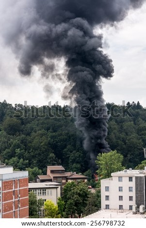 Column of black smoke rising near residential buildings. Forest fire. - stock photo