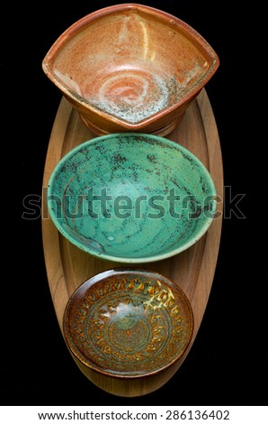 column of ceramic bowls on wooded serving tray isolated against black - stock photo