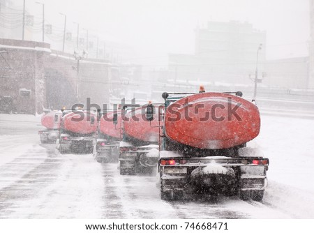 Column of five snow-remover trucks on the road in Moscow, Russia at wintertime during snowfall - stock photo