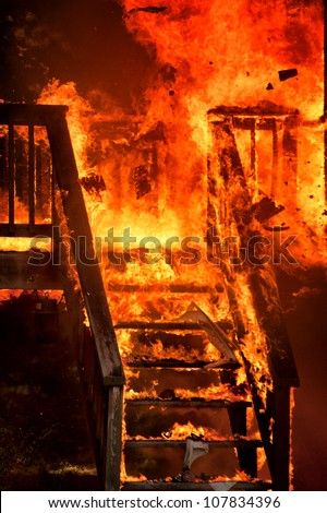 columns collapsing as house burns to ground - stock photo