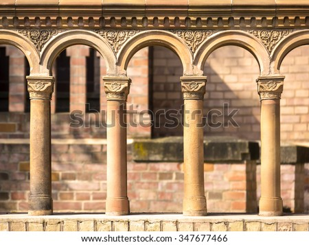 Columns in a row with terra cotta ornates, seen at a church from the early 19th century, built in the antique style.
