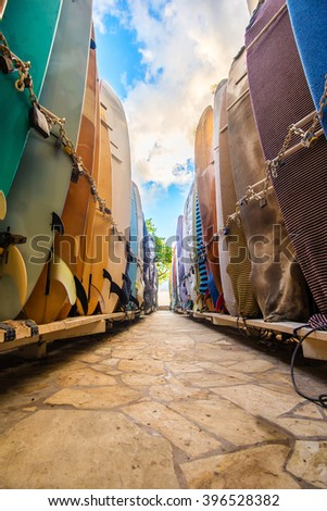 Columns of colorful surfboards in storage at Waikiki Beach - stock photo