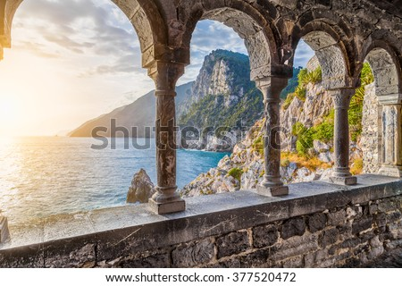 Columns of famous gothic Church of St. Peter (Chiesa di San Pietro) with beautiful shoreline scenery at sunset in the town of Porto Venere, Ligurian Coast, province of La Spezia, Italy - stock photo