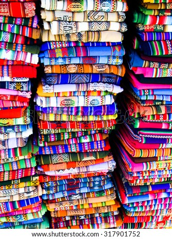 Columns of folded colorful blankets in bolivian street market, La Paz, Bolivia - stock photo