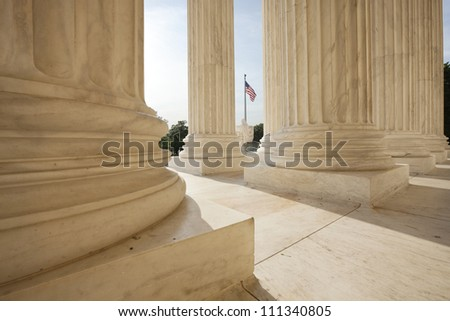 Columns of the Supreme Court building in Washington DC frame an American flag