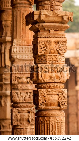 Columns with stone carving in courtyard of Quwwat-Ul-Islam mosque, Qutab Minar complex, Delhi, India, Southeast Asia - stock photo