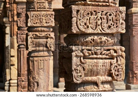 Columns with stone carving in courtyard of Quwwat-Ul-Islam mosque, Qutab Minar complex, Delhi, India - stock photo