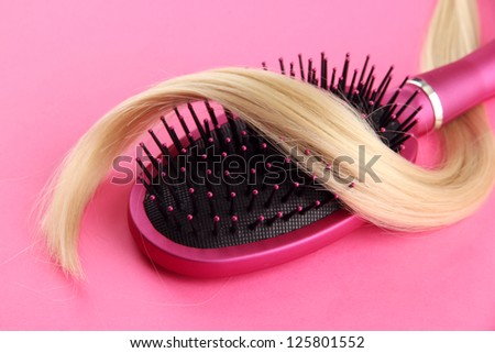 Comb brush with hair,  on pink background