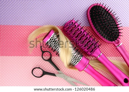 Comb brushes, hair and cutting shears, on bright background - stock photo
